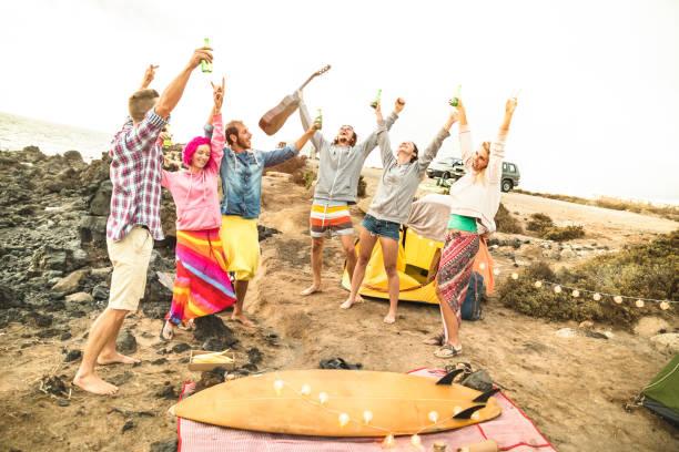 hippie-freunden spaß zusammen am strand camping music party - freundschaft reisekonzept mit jugendlichen wanderer tanzen und trinken bier im sommer surfcamp - warme helle vintage-filter - tanz camp stock-fotos und bilder