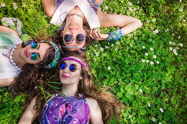 hippie freunde entspannend auf dem rasen - hippie kleider stock-fotos und bilder