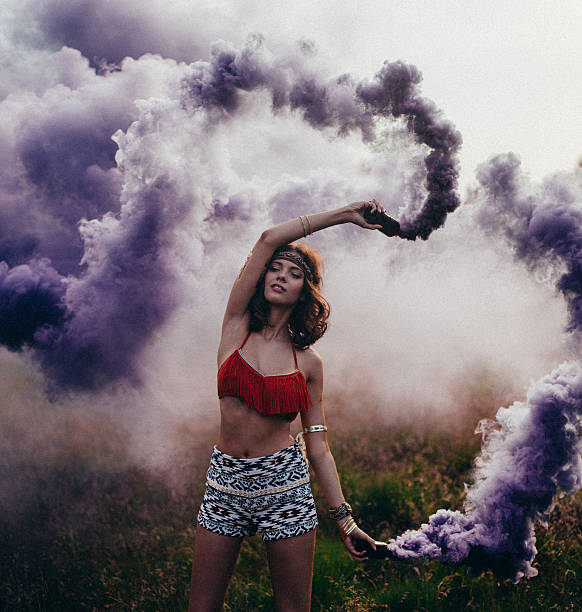 Hippie girl dancing in a park with purple smoke stock photo