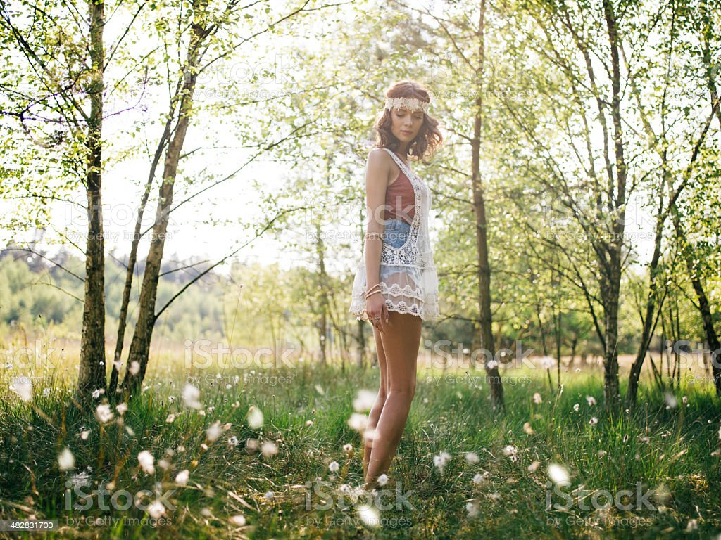 Hippie girl looking back in a summer park with flowers stock photo