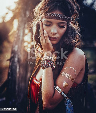Beautiful hippie girl standing outdoors with her eyes closed and wearing jewelry and a gold foil temporary tattoo