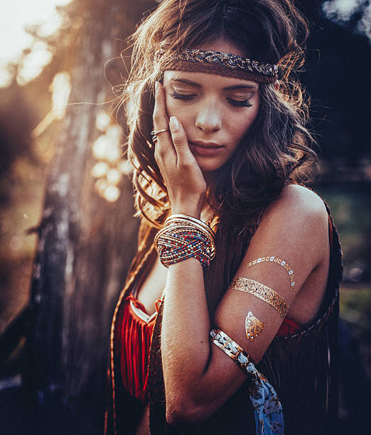 hippie girl outdoors with jewelry and temporary gold foil tattoo - hippie fashion stock photos and pictures