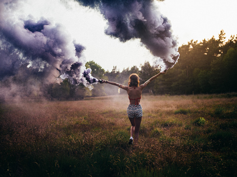 Full length rearview of a hippie girl running in field in a park carrying canisters releasing clouds of purple smoke