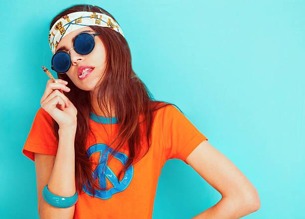 hippie girl smoking and wearing sunglasses - hippie stirnbänder stock-fotos und bilder