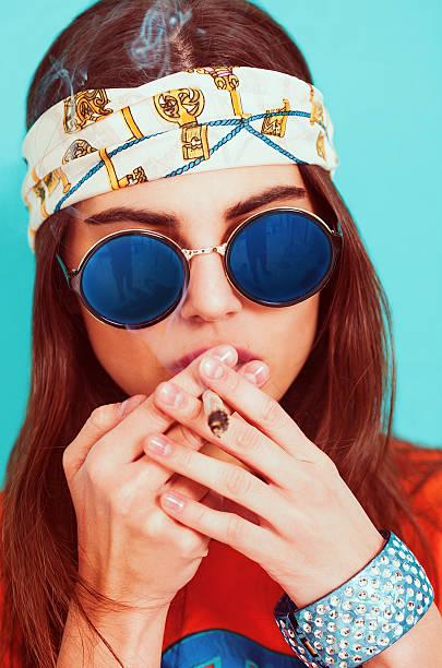 hippie girl smoking weed and wearing sunglasses - hippie stirnbänder stock-fotos und bilder