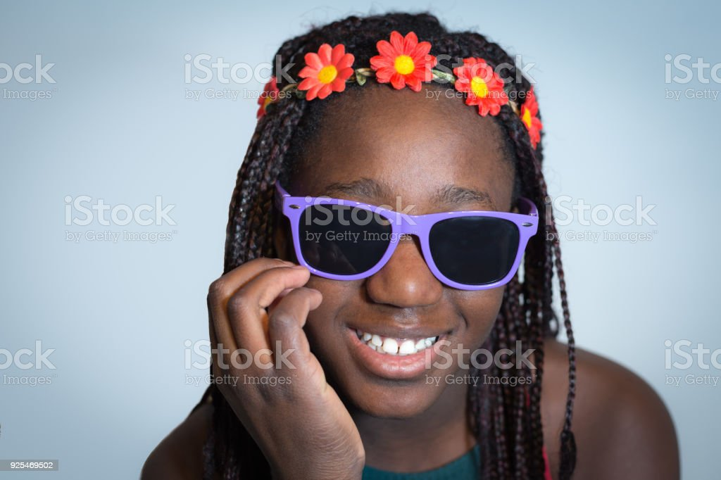 Hippie girl with floral headband and sunglasses Portrait of fashion teenager Child Stock Photo