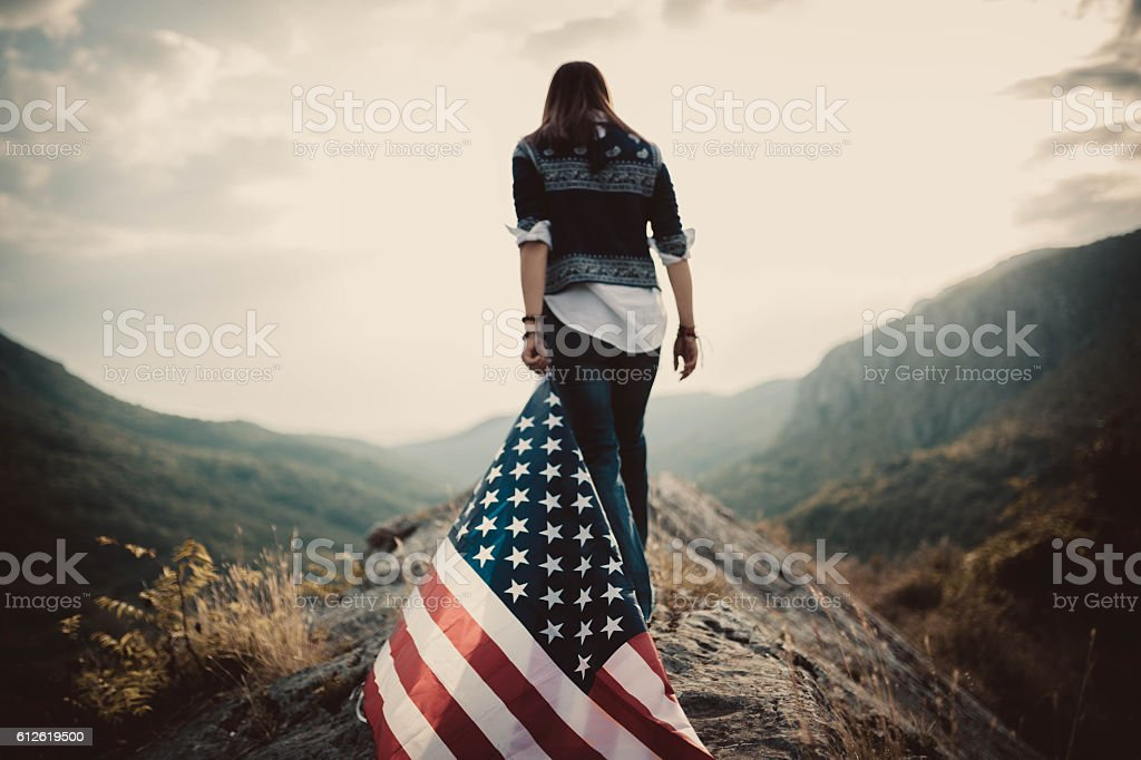 Hippie holding US flag on mountain stock photo