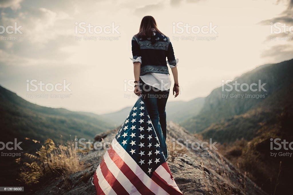 Hippie holding US flag on mountain stock photo