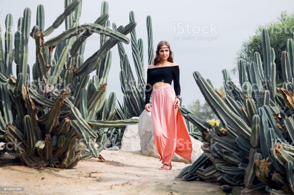 Mujer hippie en falda larga color rosa caminando cerca de grandes cactus - foto de stock