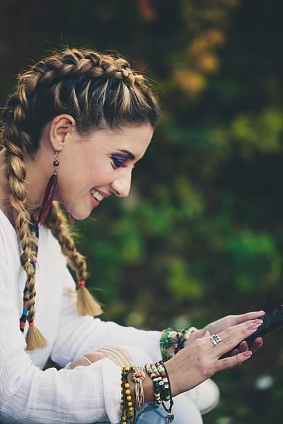 hippie woman reading a text message outdoors - frisuren 2016 frauen stock-fotos und bilder