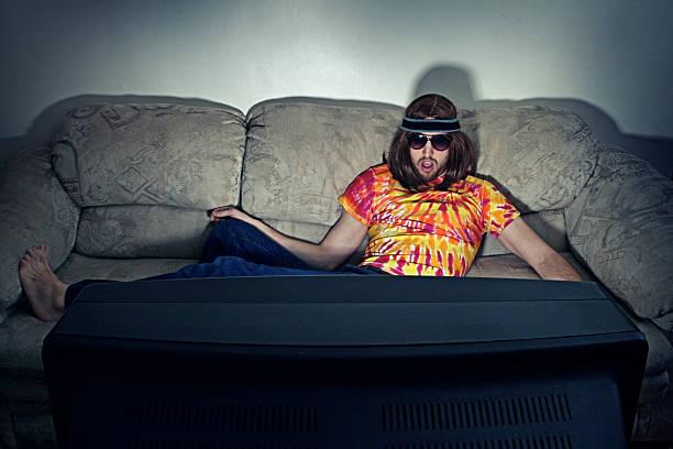 hippy fare il poltrone guardando la televisione - divano procrastinazione foto e immagini stock