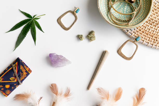 Hippy Festival Essentials on White and Wicker with Joint, Buds, Feathers, Turquoise, Marijuana Leaf, Amethyst Crystal and a Celestial Weed Pouch stock photo