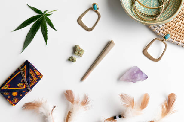 Hippy Festival Essentials on White and Wicker with Joint, Buds, Feathers, Turquoise, Marijuana Leaf, Amethyst Crystal and a Celestial Weed Pouch - Top Down stock photo