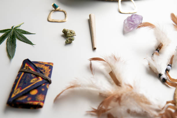 Hippy Festival Essentials on White with a Joint, Nugs, Feathers, Turquoise, Marijuana Leaf, Crystal and a Celestial Cannabis Pouch stock photo