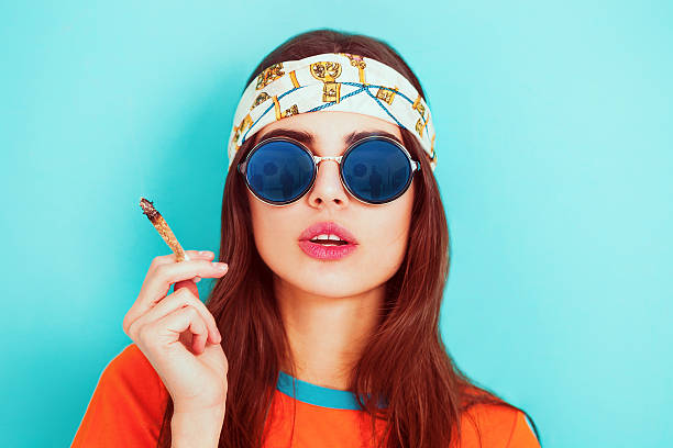 Hippy girl smoking weed and wearing sunglasses stock photo
