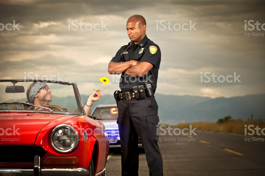 Hippy handing flower to a police officer stock photo