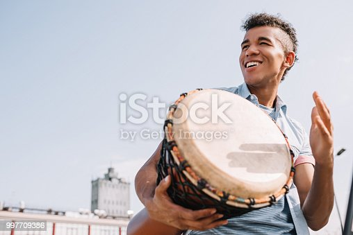 Hipster african american street drummer performing outdoors