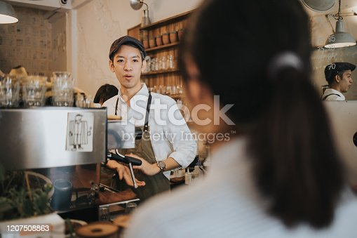 597640822 istock photo Hipster barista man just recommend the coffee menu to customer 1207508863