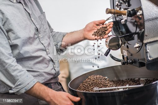 Barista running hands through the coffee beans freshly roasted at a coffee shop.
