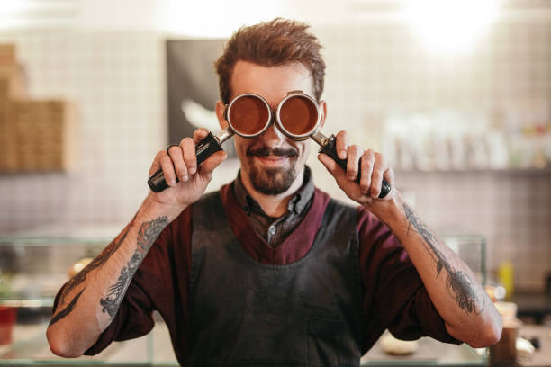 Hipster barista with portafilters in coffee shop stock photo