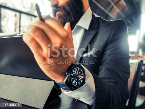 1075752640istockphoto hipster bearded adult rich businessman smoking who has smart watch using his pro tablet and work remotely 1171050272