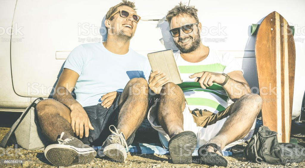 Hipster best friends having fun with tablet at car trip moment - Modern friendship and technology concept with always connected young people at alternative travel experience - Retro contrast filter stock photo