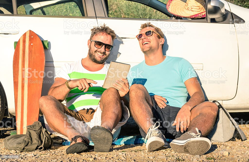 Hipster best friends having fun with tablet during car trip stock photo