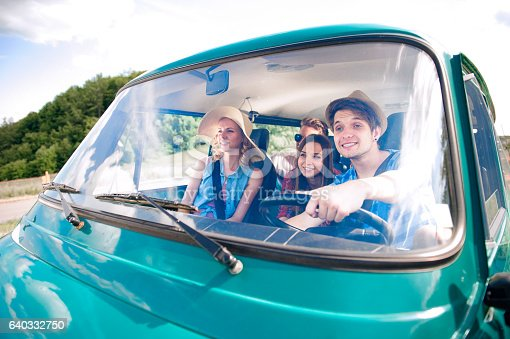 istock Hipster boy driving an old campervan with teenagers, roadtrip 640332750