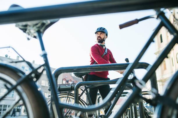hipster geschäftsmann pendler parkplatz elektro-fahrrad in die stadt, wenn sie zur arbeit zu gehen. - fahrradhalter stock-fotos und bilder