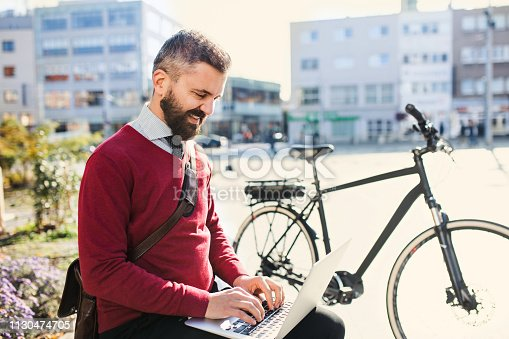 Hipster businessman commuter with bicycle on the way to work in city, sitting on a bench and using laptop.