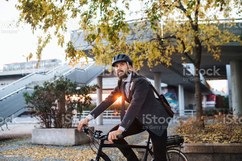Hipster businessman commuter with electric bicycle traveling home from work in city. stock photo