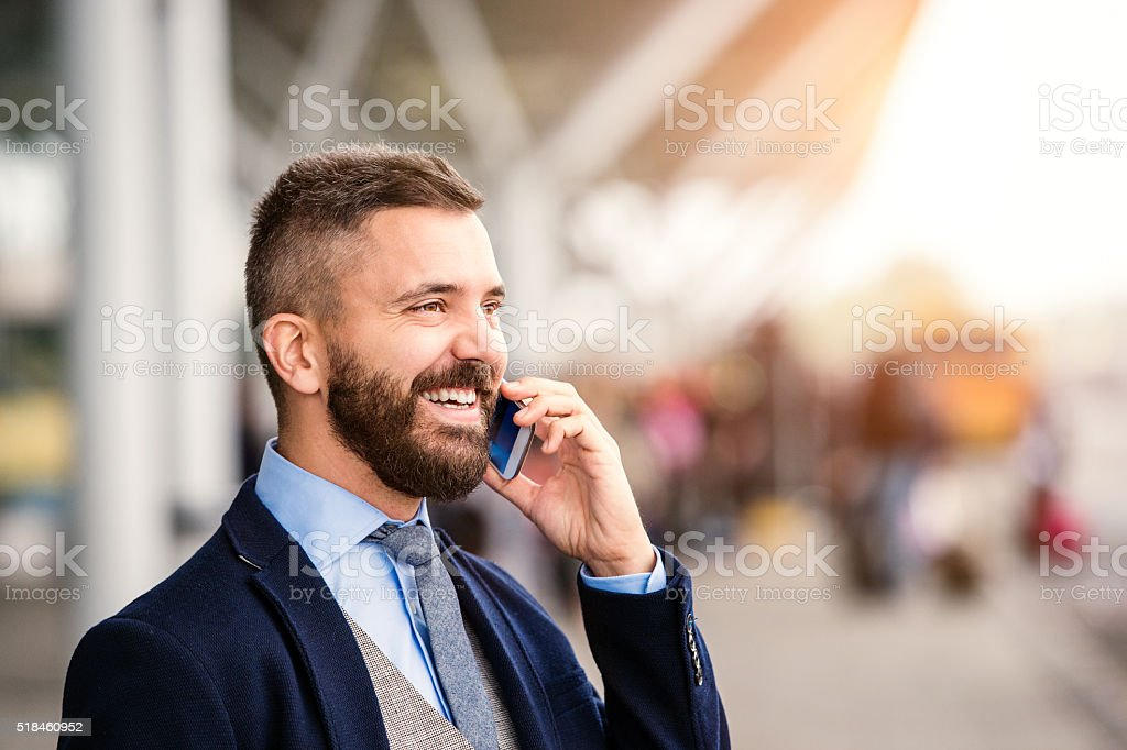 Hipster businessman making phone call waiting at the airport stock photo