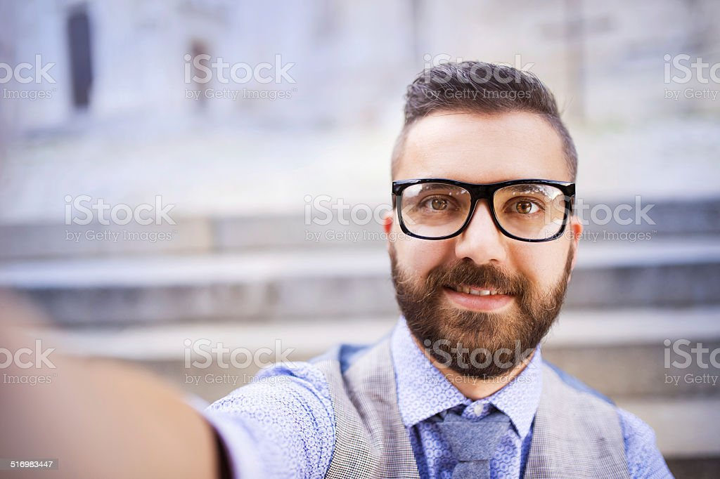 Hipster businessman taking selfie Young urban businessman taking selfie in city street Adult Stock Photo