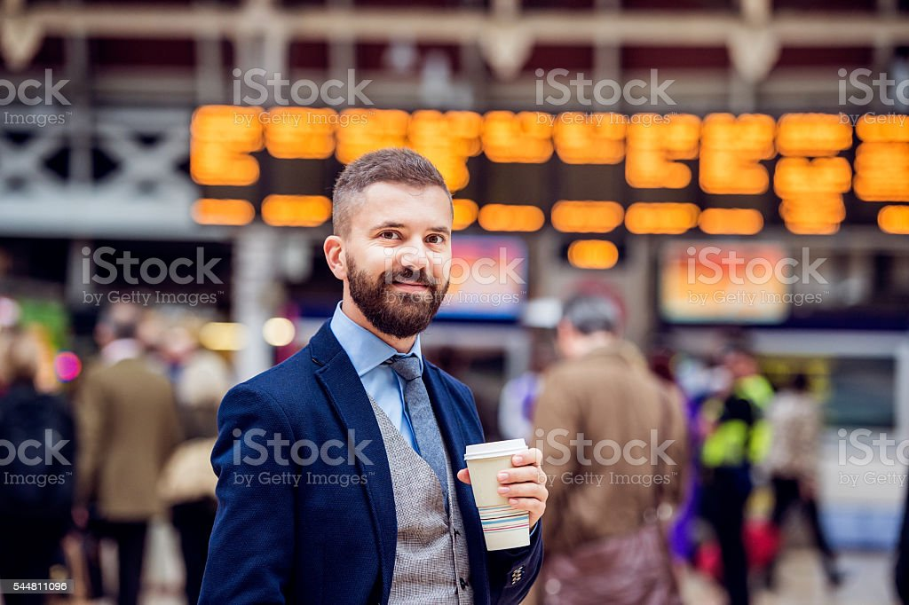 Hipster businessman with coffee cup at the train station stock photo