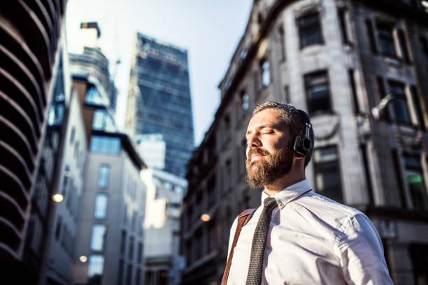 Hipster businessman with headphones standing on the street in city. Copy space. stock photo