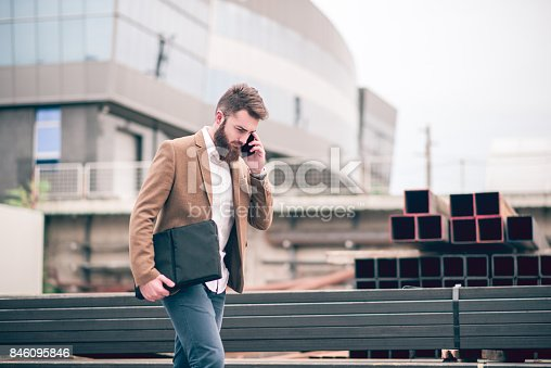 istock Hipster Businessman with Laptop Bag Talking on Mobile Phone at the Store Warehouse 846095846