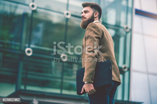 istock Hipster Businessman with Laptop Bag Walking on the City Street 625802962