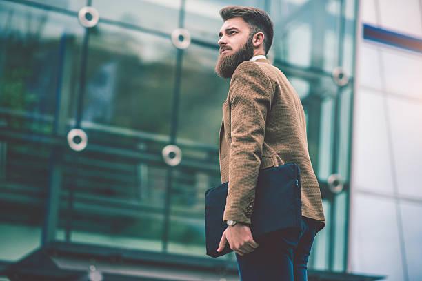 hipster businessman with laptop bag walking on the city street - moda de negocios informal fotografías e imágenes de stock