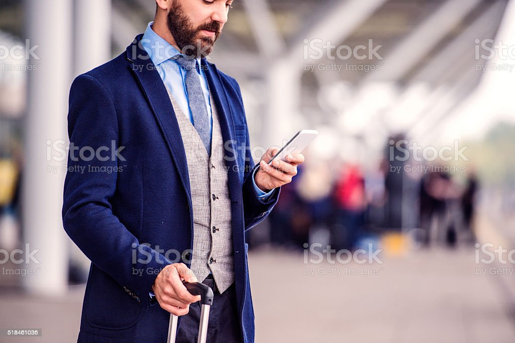 Hipster businessman with smart phone waiting at the airport stock photo