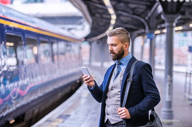 hipster businessman with smartphone, waiting at the train platfo - uk travel stock photos and pictures