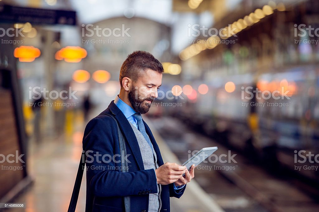 Hipster businessman with tablet, waiting, train platform stock photo