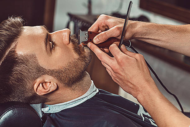 hipster client visiting barber shop - beard stock pictures, royalty-free photos & images