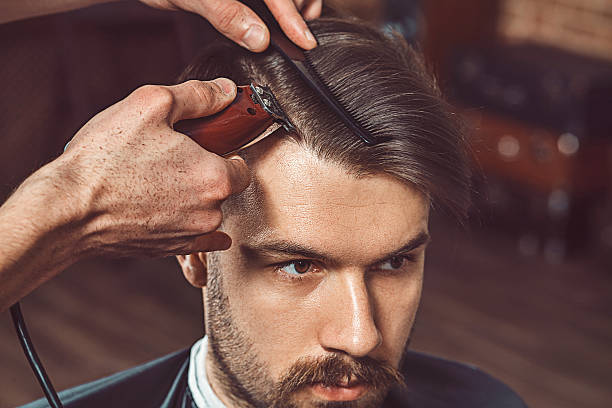 hipster client visiting barber shop - hairstyle stock photos and pictures