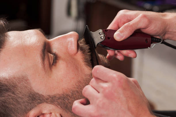 Hipster client visiting barber shop Hipster client visiting barber shop. The hands of young barber making the cut of beard shaving brush shaving cream razor old fashioned stock pictures, royalty-free photos & images