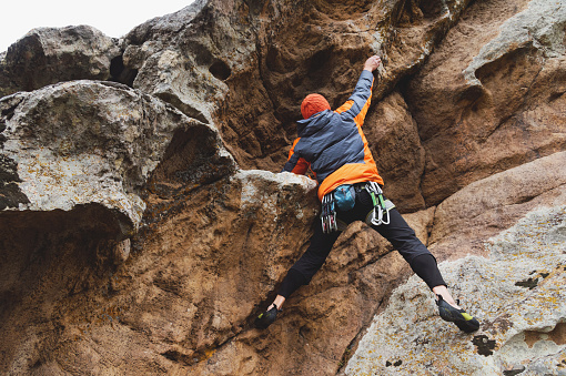 Hipster - climber at the age of climbing up a beautiful rock without insurance and helmet. A mountaineer in a hat and down jacket with a bag for magnesia and chalk on the belt and carbines. The concept of closing the mountaineering season in autumn