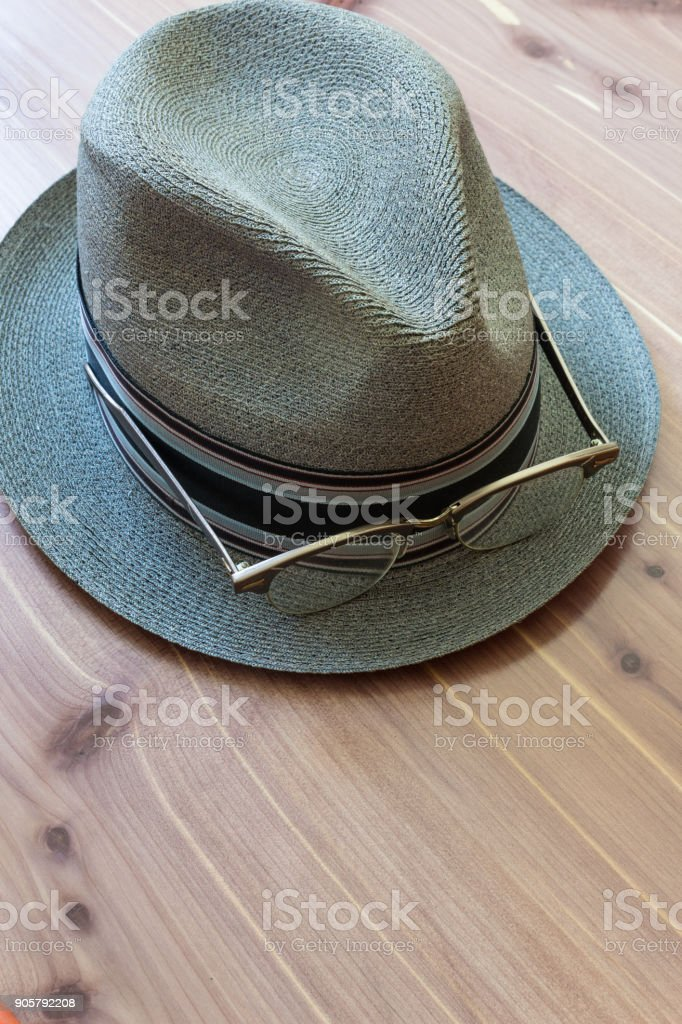 Hipster concept with fedora hat and retro horn rimmed glasses on the brim, neutral wood background stock photo
