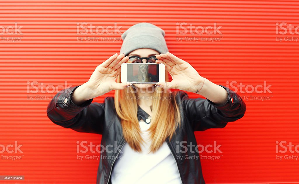 Hipster cool girl taking picture on smartphone self-portrait, sc stock photo