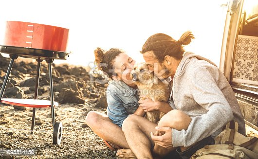 istock Hipster couple and cute dog relaxing by travel on oldtimer mini van transport - Wander lifestyle concept with indy people on minivan adventure trip having fun at barbecue moment - Warm sunshine filter 1095514150
