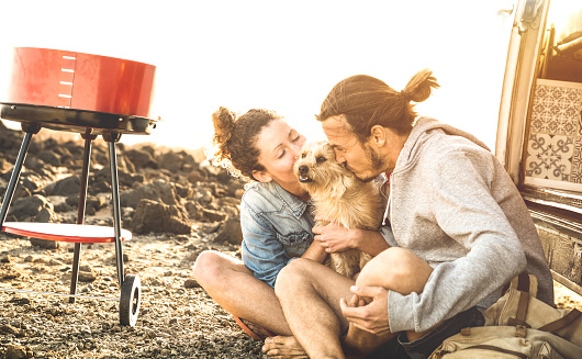 Hipster Couple And Cute Dog Relaxing By Travel On Oldtimer Mini Van Transport Wander Lifestyle Concept With Indy People On Minivan Adventure Trip Having Fun At Barbecue Moment Warm Sunshine Filter Stock Photo - Download Image Now