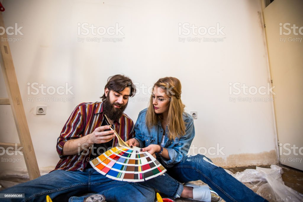 Hipster couple enjoying renovating their house stock photo